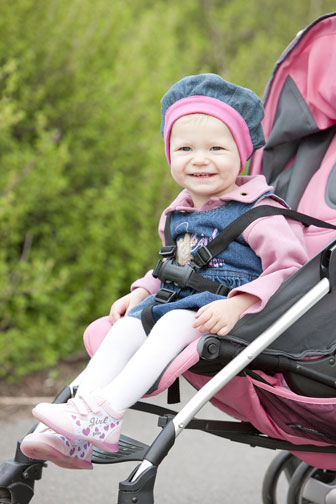 smiling toddler sitting in a stroller